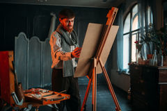 Male painter with brush in front of easel stock photography