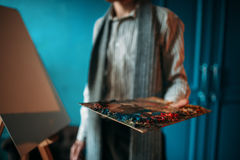 Male painter hand holds palette against the easel Royalty Free Stock Photo