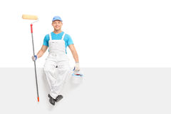 Male painter holding a paint roller seated on panel Royalty Free Stock Image
