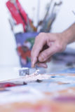 Male painter mixing paint - painting session Stock Photo