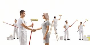 Male painter shaking hands with a young woman and workers painting wall. Full length profile shot of a male painter shaking hands with a young women and workers stock images