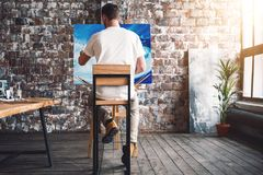 Male painter sits on chair in front canvas and drawing picture in studio. Art class and workshop. Artist painting process royalty free stock photos