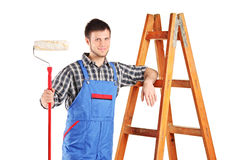 Male painter standing next to a ladder. Isolated on white background Stock Photos