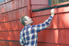 Male Painting Trim. Man in his 40s adding paint detail to the side of a front porch Royalty Free Stock Photography