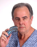 Male in pajamas using an electric razor. Morning grooming by a not-so-happy middle aged male still in his pajamas Royalty Free Stock Photo