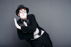 Male pantomime actor fun performing. Mime in suit, gloves, glasses, make-up mask and hat. April fools day concept Royalty Free Stock Photo