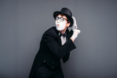 Male pantomime actor fun performing. Mime in suit, gloves, glasses, make-up mask and hat. April fools day concept stock image