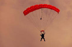Male parachutist makes the jump from the plane on red parachute. Male parachutist makes the jump from the plane on a red parachute Royalty Free Stock Images