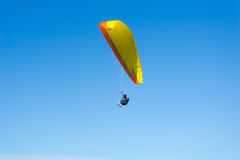 Male paraglider enjoys the freedom flying in clear blue sky abov Royalty Free Stock Photography