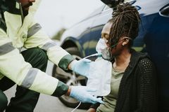 Male paramedic putting on an oxygen mask to an injured woman on a road. Male paramedic putting on an oxygen mask to an injured women on a road stock image