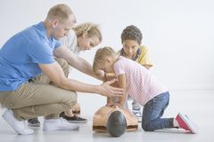 Paramedic teaching children. Male paramedic teaching little children the first aid procedures at the kindergarten royalty free stock photography