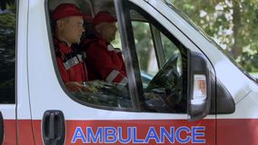Male paramedics sitting in ambulance, ready to drive out on call, professionals stock photo