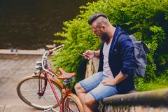 Male in a park talks by smart phone. Casual bearded male in a park talks by smart phone royalty free stock photography