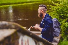 Male in a park talks by smart phone. Casual bearded male in a park talks by smart phone royalty free stock photos