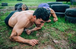 Male participant in an obstacle course crawling royalty free stock image