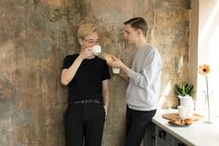 Male partners having food together. International gay couple in casual clothes drinking coffee at home stock photos