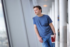 Male passenger holding passport and boarding pass at the airport Stock Photo