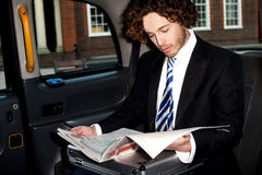 Male passenger reading newspaper in taxi Stock Image