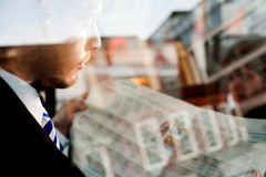 Male passenger reading newspaper in taxi Royalty Free Stock Photo