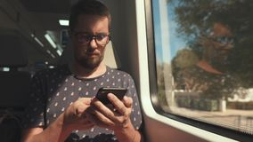 Male passenger is sending sms by mobile phone and looking in window of train stock footage