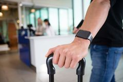 Male Passenger Wearing Smart Watch At Airport. Cropped image young male passenger wearing smart watch while holding luggage at airport Stock Images