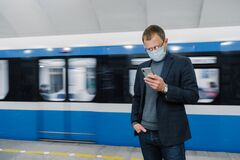 Free Male Passenger Wears Face Mask Poses At Platform, Waits For Train, Commutes By Underground, Concentrated In Smartphone Device, Royalty Free Stock Images - 177385309