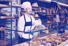 Male pastry maker demonstrating beautiful croissant stock photos