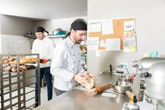 Male Pastry Makers Preparing Pastries In Kitchen. Mid adult male station chef working with fresh dough in bakery royalty free stock image