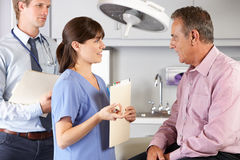 Male Patient Being Examined By Doctor And Intern Royalty Free Stock Photography