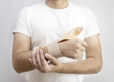 Male patient with a cast on arm, orthopedic equipment. Royalty Free Stock Photos