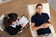 Male patient communicating while psychologist writing notes Stock Images