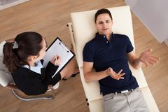 Male patient communicating while psychologist writing notes. High angle view of male patient communicating while psychologist writing notes on clipboard in Royalty Free Stock Photography