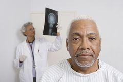 Male Patient With Doctor Examining X-Ray In Background Royalty Free Stock Photography