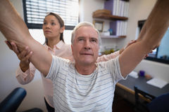 Male patient and female doctor with arms raised Stock Photo