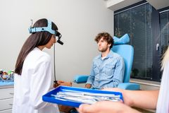 A male patient getting attended by a ENT medical specialist for. A female Ear-Nose-Throat aka ENT specialist doctor diagnosing a young male patient.r Stock Photography