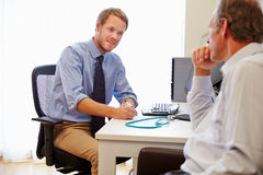 Male Patient Having Consultation With Doctor In Office stock photo