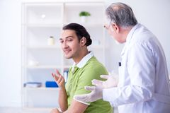 Male patient with hearing problem visiting doctor otorhinolaryng. The male patient with hearing problem visiting doctor otorhinolaryng stock photography