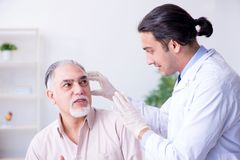 Male patient with hearing problem visiting doctor otorhinolaryng. The male patient with hearing problem visiting doctor otorhinolaryng royalty free stock photo