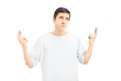Male patient in a hospital gown with fingers crossed looking upw Royalty Free Stock Photography