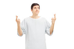 Male patient in a hospital gown with fingers crossed posing Stock Images