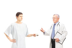Male patient in hospital gown offering bribe to a medical doctor Stock Photos