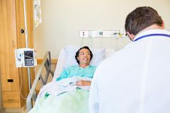 Male Patient Looking At Doctor While Lying On Stock Photography