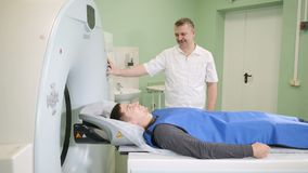 Male patient is moving into a CT-scanner. Medical equipment: computed tomography machine in diagnostic clinic. Health. Concept. Doctor presses settings button stock footage