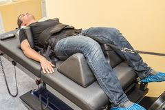 Male patient at non-surgical treatment physiotherapy of lumbar spine and spinal cord dilatation in medical center. On special medical machine equipment stock images