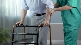 Male patient of nursing home moving with walking frame and nurse, support. Stock footage stock footage