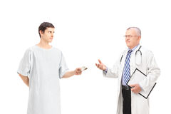 Male patient offering bribe to a mature doctor Stock Photography