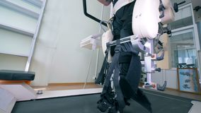 Male patient with physical impairments is exercising on a walking track simulator. Electronic medical robotic for stock video