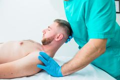 Male patient receiving massage from therapist. A chiropractor stretching his patient`s neck in medical office. Neurological. Physical examination. Osteopathy stock images