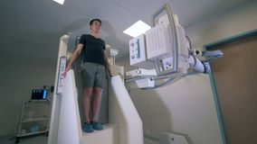 Male patient`s body is getting scanned with x-ray equipment.