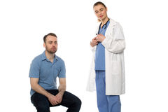 Male Patient Sitting with Standing Female Doctor Royalty Free Stock Photos